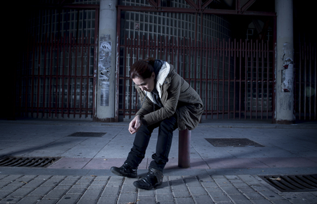 helpless: young woman alone on street suffering depression looking sad desperate and helpless sitting lonely in dirty dark urban night background in female victim of abuse concept