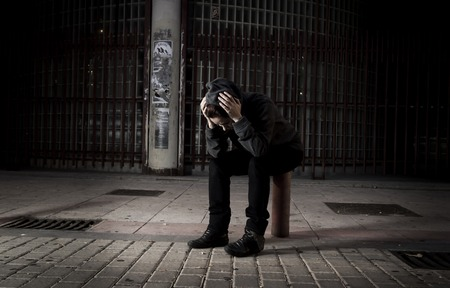 helpless: young sad woman alone wearing hoodie on street suffering depression looking  desperate and helpless sitting lonely in urban night background in female victim of abuse concept