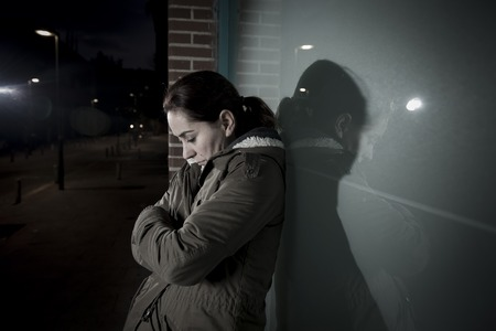victim: young sad woman alone leaning on street window at night looking desperate suffering depression crying in pain lonely and lost as violence and abuse female victim or addict concept Stock Photo