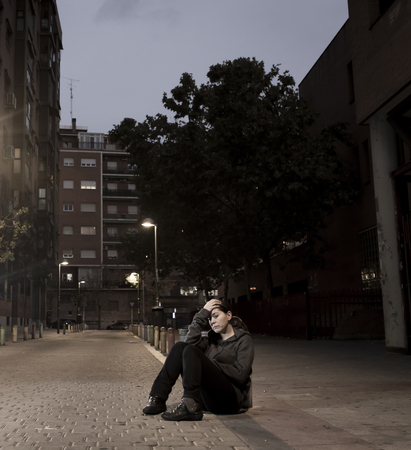 sitting on the ground: young sad woman sitting on street ground at night alone desperate suffering depression left abandoned and lost in grunge urban background as abuse and violence female victim or addict concept Stock Photo