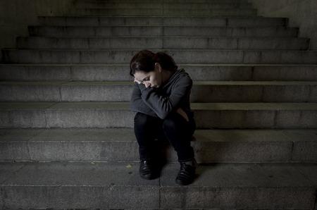 depresión: triste mujer sola en la calle escalera del subterráneo sufrimiento depresión buscando enfermos y desvalidos sentarse solo como mujer víctima de maltrato en concepto oscura noche urbana grunge de fondo Foto de archivo