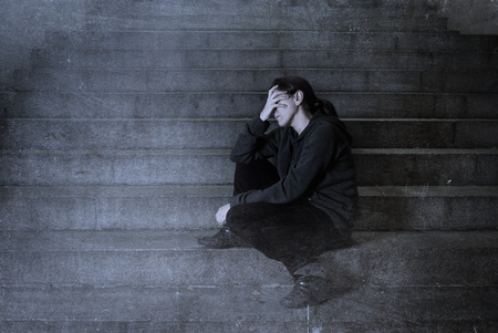 sad woman alone on street subway staircase suffering depression looking sick and helpless sitting lonely as female victim of abuse concept  in  dark urban night grunge background grunge dirty edit Stock fotó