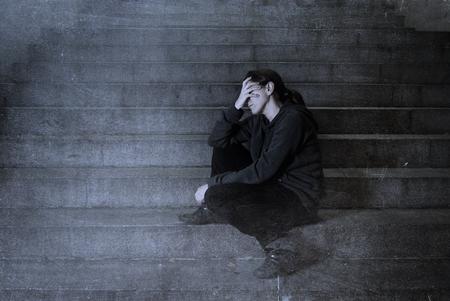 depresión: triste mujer sola en la calle escalera del subterráneo sufrimiento depresión buscando enfermos y desvalidos sentarse solo como mujer víctima de maltrato en concepto oscuro urbano noche grunge fondo del grunge editar sucia
