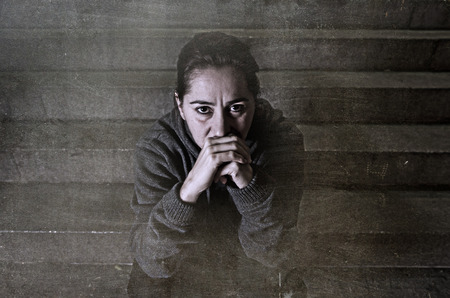 alone: sad woman alone on street subway staircase suffering depression looking sick and helpless sitting lonely as female victim of abuse concept  in  dark urban night grunge background grunge dirty edit Stock Photo