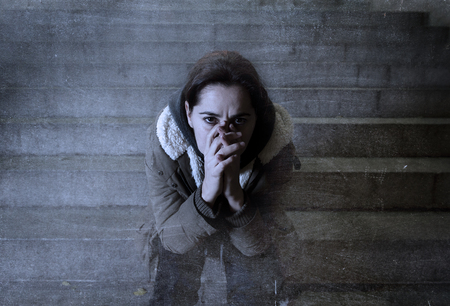 girl sit: sad woman alone on street subway staircase suffering depression looking sick and helpless sitting lonely as female victim of abuse concept  in  dark urban night grunge background grunge dirty edit Stock Photo