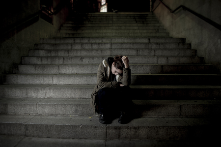 frustration girl: sad woman alone on street subway staircase suffering depression looking sick and helpless sitting lonely as female victim of abuse concept  in  dark urban night grunge background