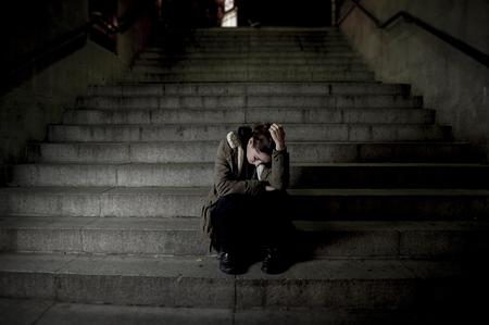 Triste mujer sola en la calle escalera del subterráneo sufrimiento depresión buscando enfermos y desvalidos sentarse solo como mujer víctima de maltrato en concepto oscura noche urbana grunge de fondo Foto de archivo - 48469153