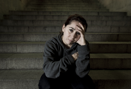 helpless: sad woman alone on street subway staircase suffering depression looking sick and helpless sitting lonely as female victim of abuse concept  in  dark urban night grunge background