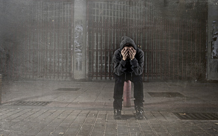 sad woman alone wearing hoodie on street suffering depression looking  desperate and helpless sitting lonely in urban night background in female victim of abuse concept grunge dirty edit Stock Photo - 48469161