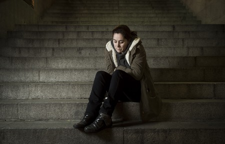 girl sit: sad woman alone on street subway staircase suffering depression looking sick and helpless sitting lonely as female victim of abuse concept  in  dark urban night grunge background
