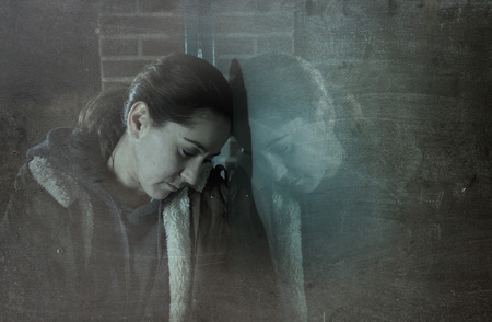 addiction alone: sad woman alone leaning on street window at night looking desperate suffering depression crying in pain lonely and lost as violence and abuse female victim or addict concept grunge dirty edit