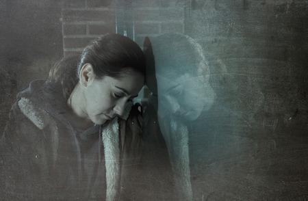 persona deprimida: triste mujer sola apoyado en la ventana de la calle por la noche buscando la depresión sufrimiento desesperado llorando de dolor solo y perdido como la violencia y el abuso víctima femenina o adicto concepto grunge editar sucia Foto de archivo