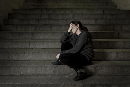 ansiedad: triste mujer sola en la calle escalera del subterr�neo sufrimiento depresi�n buscando enfermos y desvalidos sentarse solo como mujer v�ctima de maltrato en concepto oscura noche urbana grunge de fondo Foto de archivo