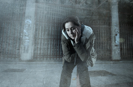 sad lonely girl: sad woman alone on street suffering depression looking desperate and helpless sitting lonely in dirty dark urban night background in female victim of abuse concept grunge dirty edit grunge dirty edit Stock Photo