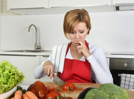 cut and blood: young attractive home cook woman in red apron slicing tomato with kitchen knife  suffering domestic accident cutting and hurting her finger while cooking in pain face expression licking blood Stock Photo