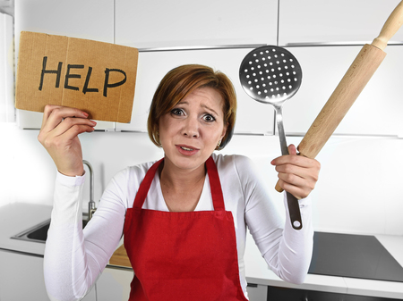 messy kitchen: young desperate inexperienced home cook woman crying in stress feeling desperate holding rolling pin and help sign at domestic kitchen in rookie messy cooking and lifestyle concept