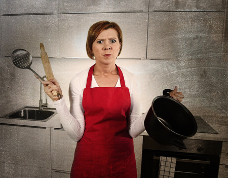 confused: young beautiful cook woman confused and frustrated face expression wearing red apron holding rolling pin and cooking pot at home kitchen in domestic stress and lifestyle concept grunge dirty edit Stock Photo