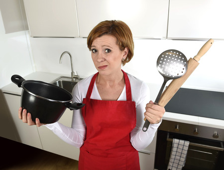 confused face: young attractive rookie home cook woman in red apron at home kitchen holding cooking pan and rolling pin sad in stress confused and helpless in lifestyle and cooking mess