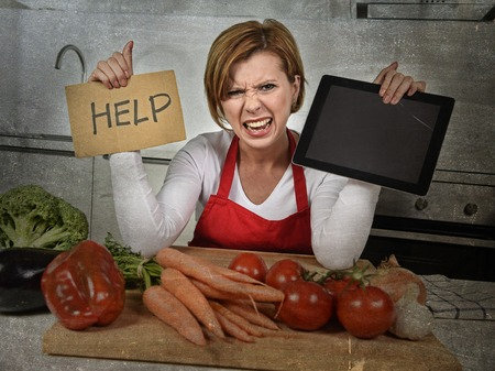 cry for help: inexperienced home cook woman in red apron screaming desperate and frustrated at domestic kitchen in stress holding digital tablet asking for help in amateur and rookie cooking mess Stock Photo