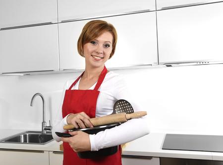 mandil: la mujer del cocinero dulce que llevaba delantal rojo sosteniendo la olla de cocción y rodillo en la cocina el país que sonríe feliz en la cocina doméstica y estilo de vida concepto