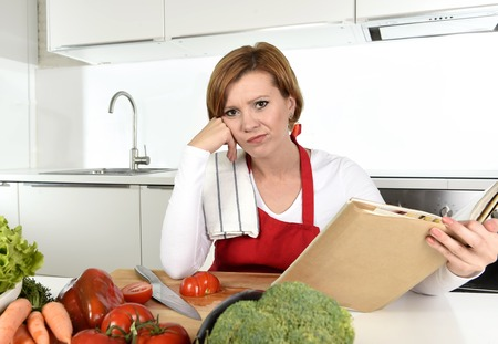 expressive face: young beautiful cook woman bored and confused wearing red apron sitting at home kitchen reading recipes book bored and confused in domestic stress and lifestyle concept
