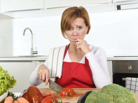 young attractive home cook woman in red apron slicing tomato with kitchen knife  suffering domestic accident cutting and hurting her finger while cooking in pain face expression licking blood Stockfoto