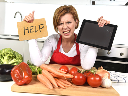 inexperienced: inexperienced home cook woman in red apron screaming desperate and frustrated at domestic kitchen in stress holding digital tablet asking for help in amateur and rookie cooking mess Stock Photo