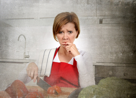 sad lady: young attractive home cook woman in red apron slicing tomato with kitchen knife  suffering domestic accident cutting and hurting her finger while cooking in pain face expression licking blood Stock Photo