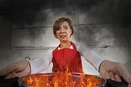 jonge onervaren thuiskok vrouw in paniek met schort met pot branden in vlammen met stress en paniek gezichtsuitdrukking in brand in de keuken en amateur newbie rookie ad rommelig koken begrip Stockfoto