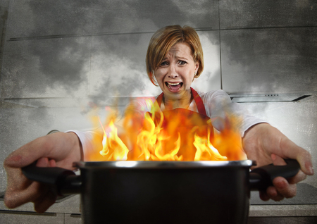 terrorized: young inexperienced home cook woman in panic with apron holding pot burning in flames with stress and panic face expression in fire in the kitchen and amateur newbie rookie ad messy cooking concept