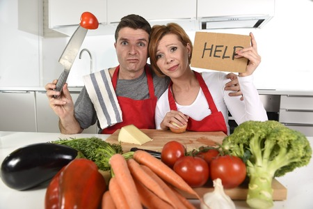 inexperienced: young attractive American couple in stress at home kitchen looking lost and frustrated wearing apron asking for help unable to cook in amateur newbie inexperienced and rookie home cooking mess