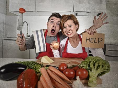jonge aantrekkelijke Amerikaanse koppel in stress thuis keuken op zoek verloren en gefrustreerd dragen schort vragen om hulp niet in staat om te koken in de amateur-newbie onervaren groentje thuis koken puinhoop Stockfoto