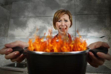 catastrophe: jeune inexp�riment� femme maison de cuisinier dans la panique avec tablier, tenue, pot br�ler dans les flammes avec le stress et la panique face � l'expression dans le feu dans la cuisine et amateur d�butant recrue ad concept de cuisine en d�sordre