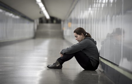 young sad woman in pain sitting alone and depressed at urban subway tunnel ground looking worried and frustrated suffering depression in female loneliness concept Imagens