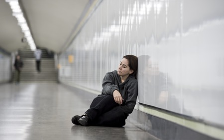 girl alone: young sad woman in pain sitting alone and depressed at urban subway tunnel ground looking worried and frustrated suffering depression in female loneliness concept Stock Photo