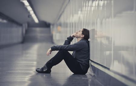 jonge trieste vrouw in pijn zitten alleen en depressief op stedelijk metrotunnel grond op zoek bezorgd en gefrustreerd lijden depressie bij vrouwelijke eenzaamheid begrip