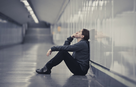 young sad woman in pain sitting alone and depressed at urban subway tunnel ground looking worried and frustrated suffering depression in female loneliness concept Foto de archivo