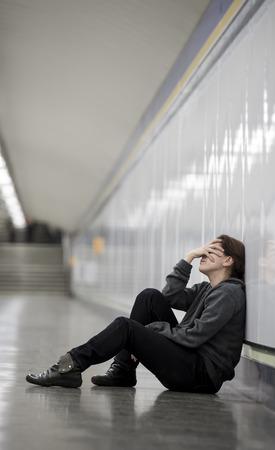 mujer triste: joven mujer triste en el dolor sentado solo y deprimido en la planta t�nel del metro urbano con cara de preocupaci�n y frustrada que cubre su rostro sufrir depresi�n en mujeres concepto de la soledad