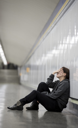 girl sit: young sad woman in pain sitting alone and depressed at urban subway tunnel ground looking worried and frustrated covering her face suffering depression in female loneliness concept Stock Photo