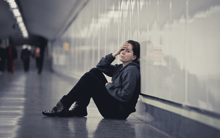 sitting on the ground: young sad woman in pain sitting alone and depressed at urban subway tunnel ground looking worried and frustrated covering her face suffering depression in female loneliness concept Stock Photo