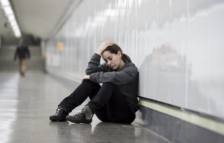 sitting on the ground: young sad woman in pain sitting alone and depressed at urban subway tunnel ground looking worried and frustrated suffering depression in female loneliness concept Stock Photo