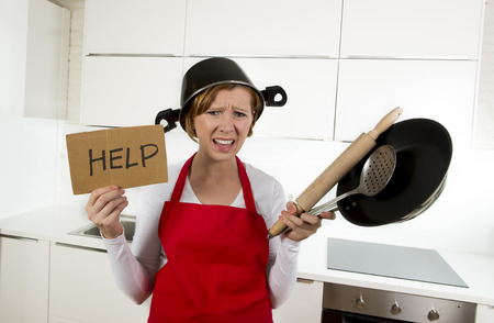 inexperienced: young attractive home cook woman in red apron at  kitchen holding pan and household with pot on her head in stress frustrated face expression in rookie amateur and inexperienced cooking concept