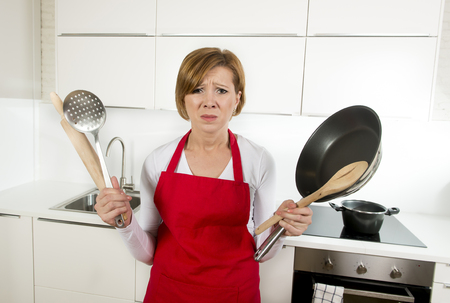 sad lady: young attractive home cook woman in red apron at domestic kitchen holding pan and household in stress with desperate and frustrated face expression in rookie amateur and inexperienced cooking