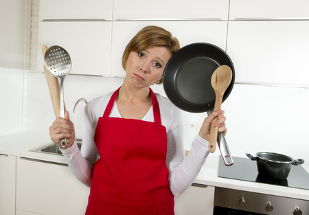 inexperienced: young attractive home cook woman in red apron at domestic kitchen holding pan and household in stress with desperate and frustrated face expression in rookie amateur and inexperienced cooking