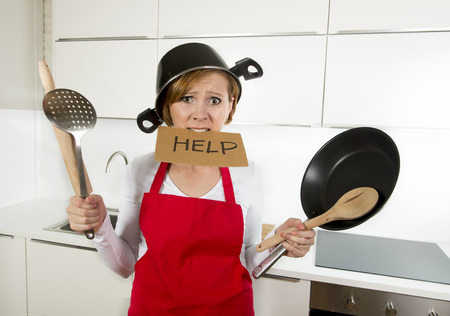young attractive home cook woman in red apron at  kitchen holding pan and household with pot on her head in stress frustrated face expression in rookie amateur and inexperienced cooking concept