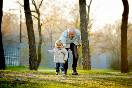hispanic kids: young happy father and his beautiful little 2 years old son walking together on Autumn park with trees having fun playing and sharing a sunny day in family love and childhood concept