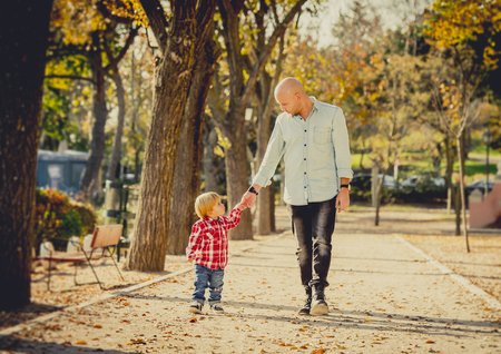 guy portrait: young happy father and his beautiful little 2 years old son walking together on Autumn park with trees having fun playing and sharing a sunny day in family love and childhood concept