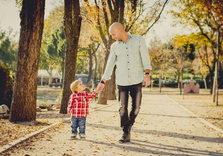 2 years old: young happy father and his beautiful little 2 years old son walking together on Autumn park with trees having fun playing and sharing a sunny day in family love and childhood concept