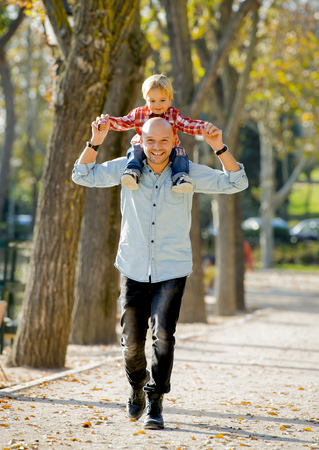 shoulder carrying: young attractive father carrying his happy little son on his shoulder walking together having fun on the park in Autumn sunny day smiling happy in family love and childhood concept