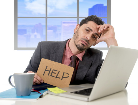 overwork: young businessman working on computer laptop asking for help holding cardboard sign looking desperate and depressed in stress overwhelmed and overwork at business district office